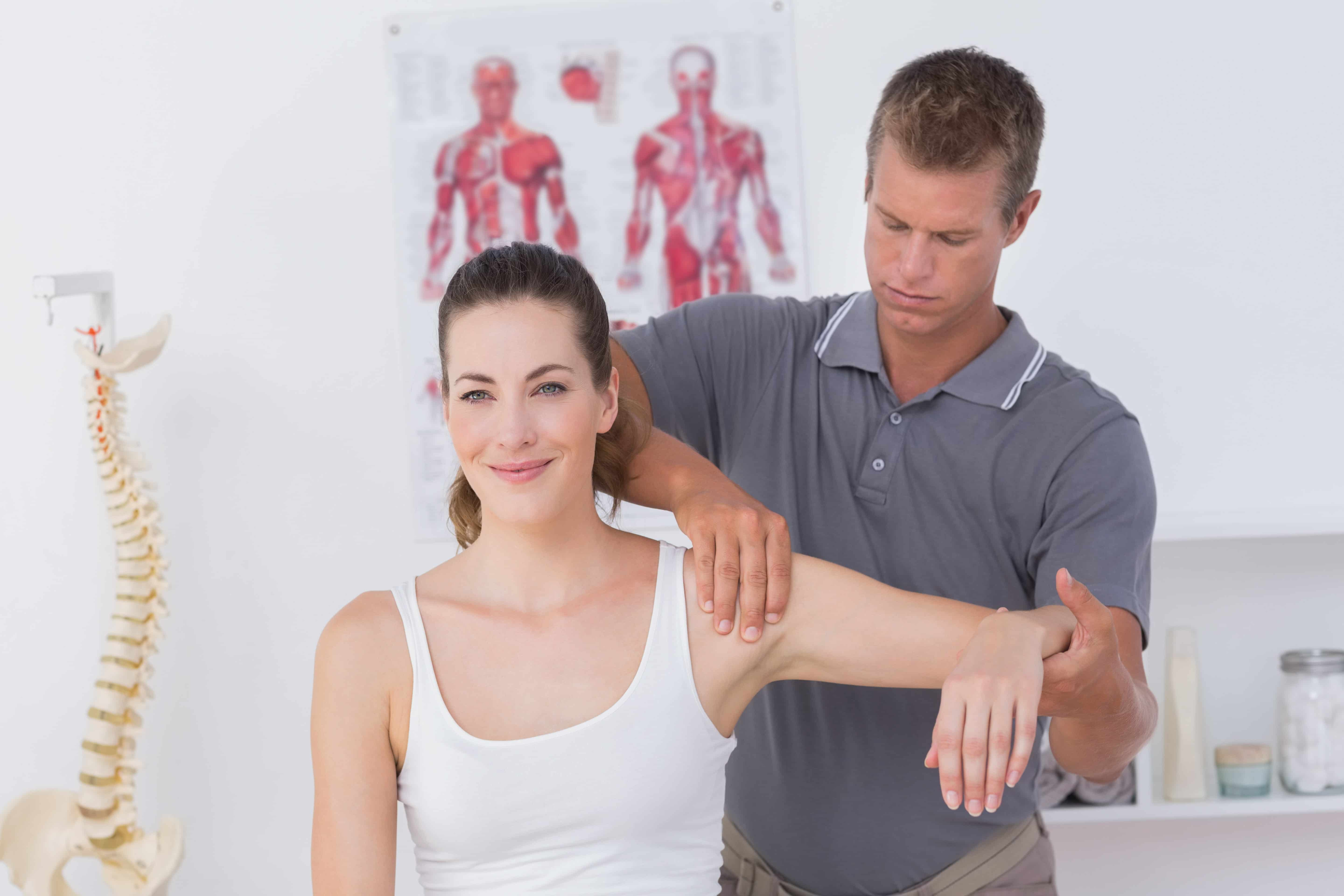 Woman getting her arm stretched by physical therapist